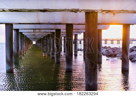 Ferroconcrete pillars of pedestrian seaside pier set in water on coast of Baltic sea. Sunset at Baltic sea in resort Palanga Lithuania. Industrial & civil architectural design in difficult conditions