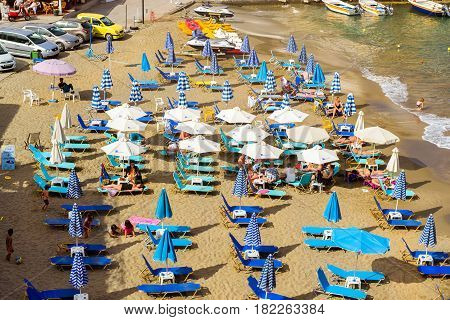 Bali Greece - April 30 2016: Sandy Mithos beach in sea bay of resort village Bali. Views of shore washed by waves and sun loungers with parasols where sunbathing tourists. Rethymno Crete Greece