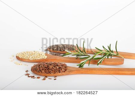 Healthy grains including flax seed, white grain quinoa and chia seed in wooden spoons