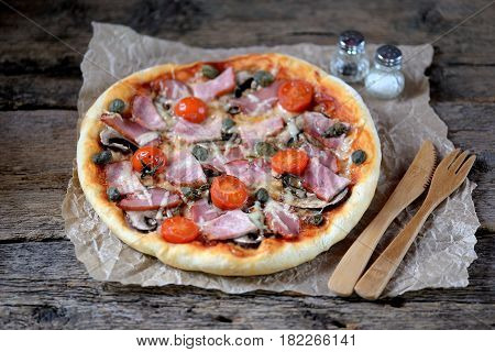 Homemade pizza with smoked meat, ham, mushrooms, cherry tomato, capers and cheese.