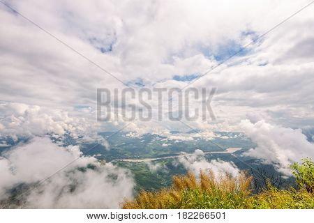 Beautiful natural landscape from high angle view of Mekong River forest and white clouds in the sky on the mountain at Doi Pha Tang view point Chiang Rai Province Thailand