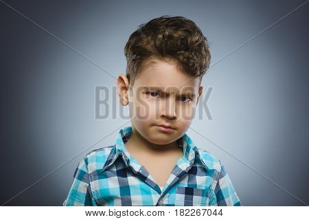 Portrait of angry boy isolated on gray background.