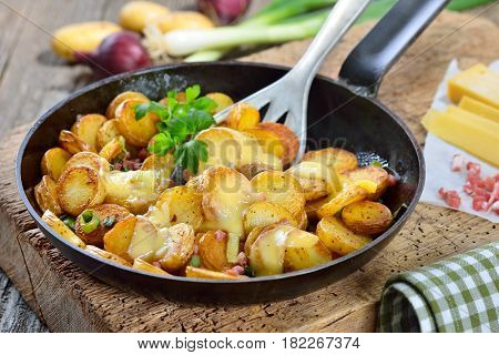 Fried unpeeled baby potatoes with melted mountain cheese and bacon cubes