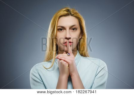 woman placing finger on lips asking shh, quiet, silence on gray background.