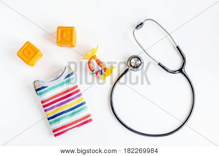 stethoscope, toys on children's doctor office white desk background top view