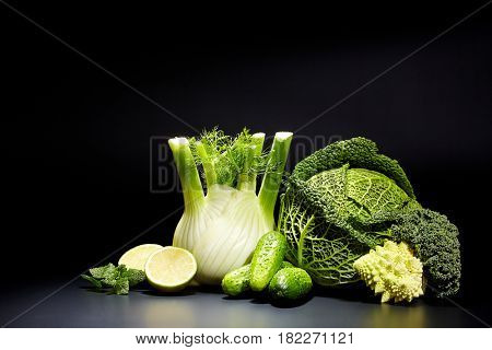 studio photo of different green vegetables on black background