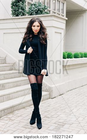 Long-legged brunette girl with long hair, in black outfit, high black boots on heels posing on the street of a European city. Fashion. Style.