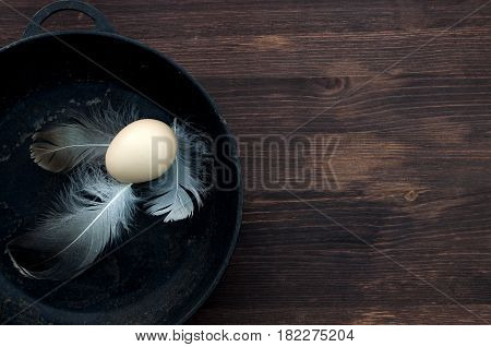One raw hen's egg in the shell the egg lies in a black cast-iron frying pan the free space on the right