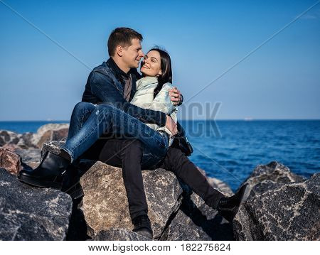 emotional couple sitting on the rocks on the beach with ocean on background. She is sitting on his lap and smiling
