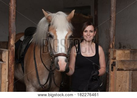 Young Woman Holding Her Horse In Stable