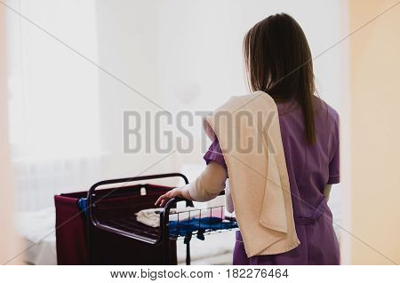 Young Female Maid pushing cart While Cleaning Hotel Rooms.
