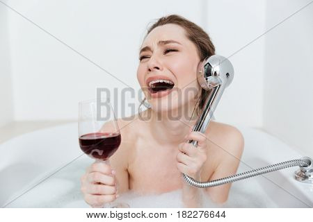 Sad disappointed young woman with glass of wine crying and playing with shower in bathtub