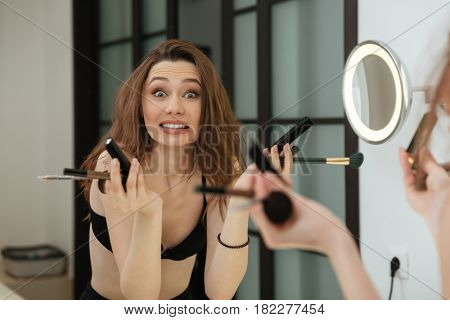 Confused pretty young woman holding brushes and doing makeup in bathroom