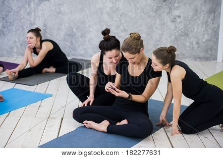 Cute girl sitting and socializing with the group after their yoga class.