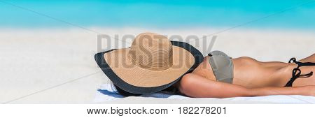 Beach relaxation woman sleeping with hat banner sun tanning covering her face with sunhat for uv solar protection on blue ocean background. Vacation girl relaxing resting on summer travel.