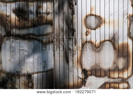 Charred wall of metal profile after a fire. Abstract background with stains for design