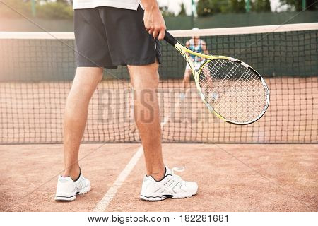 Legs of tennis man on court with racket. cropped image