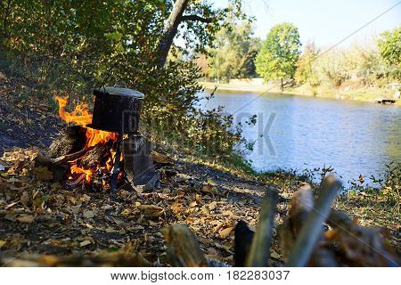 Black bowler hat with ear on the fire near the lake