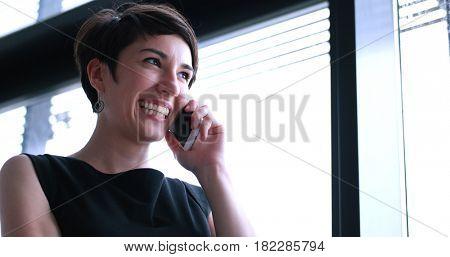 businesswoman speeking on phone beside window of modern office