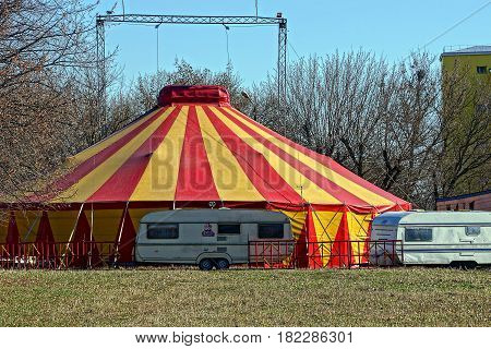 Bright colored tent circus and car trailers