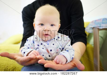 Little smiling baby is in hands of father in room, shallow dof