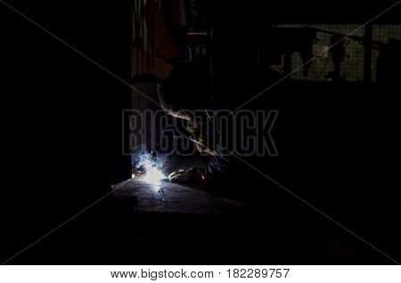 Worksman welding wrought iron metal rods together in dark workshop with blue smoke and orange sparks wearing protective UV eyewear gear for eye protection