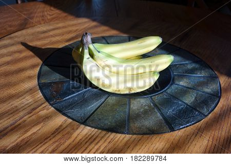 A bunch of bananas sits in the center of a round Lazy Susan dining table.