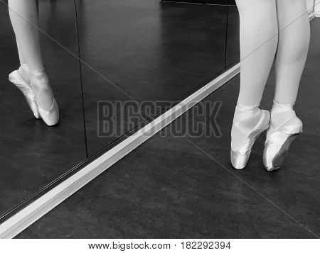 Black and white image of legs of young ballerina on pointe in a ballet dancing studio with a reflection in the mirror and space for text.