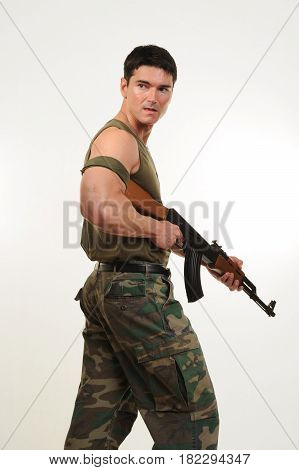 The tough army man is holding a rifle.