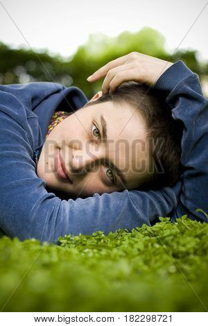 Portrait Of A Beautiful Girl With Short Hair And Green Eyes Lies On The Grass, Smiling And Looking A