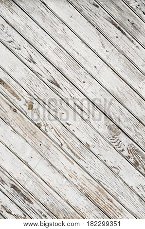 Old wooden gate is covered with shabby white paint. Background.