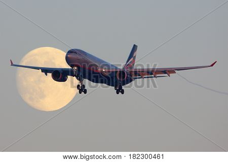 SHEREMETYEVO, MOSCOW REGION, RUSSIA - NOVEMBER 29, 2013: Aeroflot Airbus A330 VQ-BBF crossing the moon before landing at Sheremetyevo international airport.