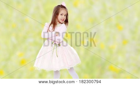Dressy little girl long blonde hair, beautiful pink dress and a rose in her hair.One folded his arms.Summer white green blurred background.