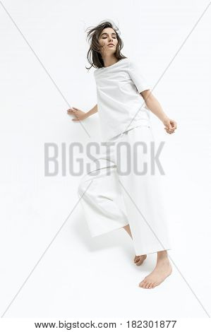Barefoot girl with windy hair is posing in the studio on the white background. She wears a white T-shirt and pants. Woman leans on the wall in the motion. Vertical.