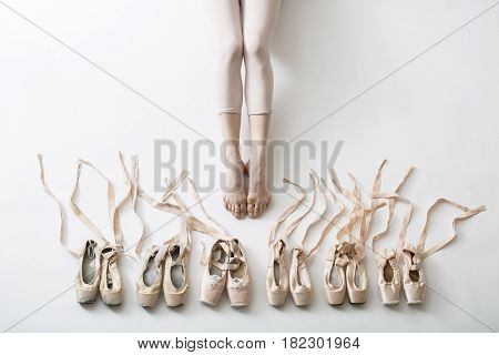 Many pairs of ballet shoes in pairs stand in a row. Legs of a young ballerina with bare feet. The girl's fingers are all covered in wounds and plasters. Pointe shoes in different condition from new to very shabby old. Tapes are accurately laid out in diff