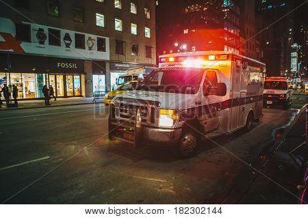 New York City USA - March 18 2017: FDNY Ambulance flashing lights siren blasting speed through midtown rush hour traffic in Manhattan.