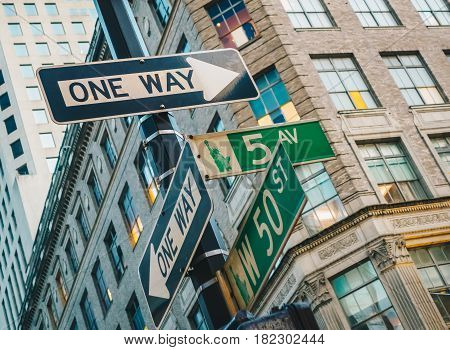 Street sign of Fifth Ave and West 50ST with skylines in background.- New York USA
