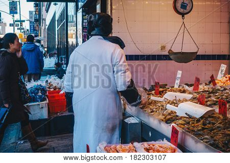 New York City USA - March 19 2017 : Facades of house and shops in China town.Typical Chinese food market