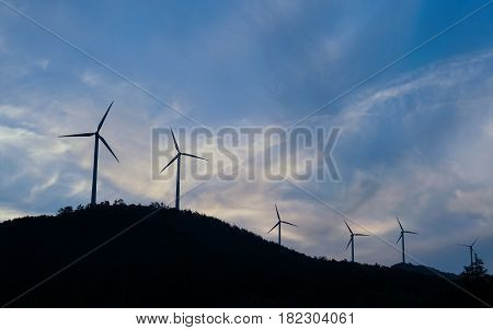 Wind turbines, wind farms silhouette at sunset