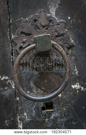 Antique ring shaped metal door knocker on old door in Toulouse, France, closeup.