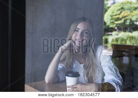Young smiling woman sitting in cafe with coffee photographed through window glass from outside