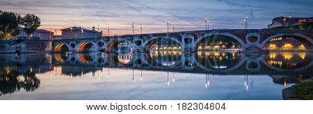 Evening panorama of historic Pont Neuf in Toulouse, France, with illuminated arches over Garonne River.