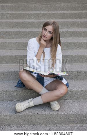 Young thoughtful female student sitting on stairs, blonde caucasian girl holding a textbook looking to the side