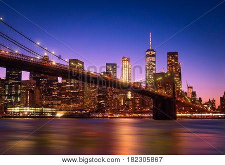 View of Brooklyn Bridge and Manhattan skyline WTC Freedom Tower from Dumbo by night Brooklyn. Brooklyn Bridge is one of the oldest suspension bridges in the USA