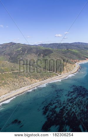 Aerial view of mountains, ocean kelp and Pacific Coast Highway north of Malibu in Southern California.