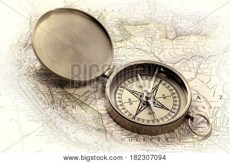 vintage pocket brass compass over old map, retro hand tinted opalotype processing