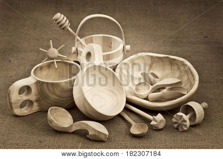 Polish folk wood craft (cups, bowl, spoons, scoops, bucket, kitchen utensils, butter mold, honey drizzler) on burlap background, sepia toned black and white image