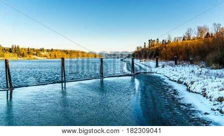 Mooring pylons along the Fraser River at Fort Langley, British Columbia, Canada on a cold winter day under a clear blue sky