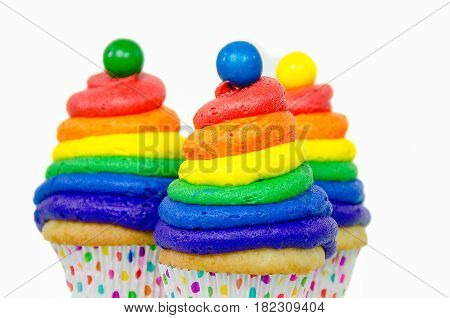 rainbow swirled frosting and gumball on cupcake isolated on white