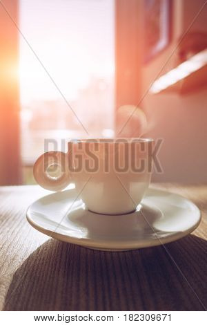 Hot Cappuccino coffee on the table with blurry kitchen background with sun flare vintage tone